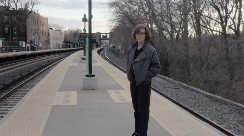 Paige (Holly Taylor) standing on the train platform after abandoning her parents.