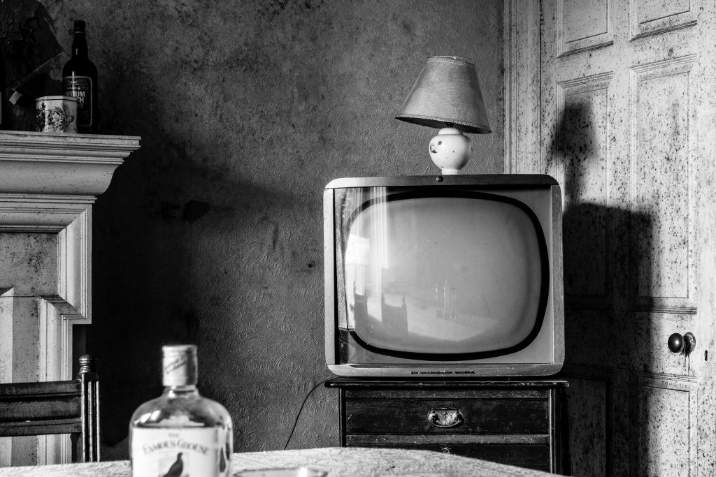 Black-and-white photo of a television and whiskey bottle.